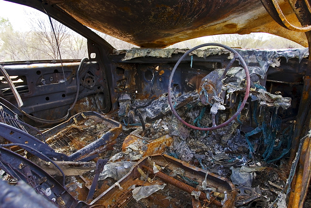 Inside burnt-out car wreck on road from Alice Springs,  Namatjira Drive, Northern Territory, Australia