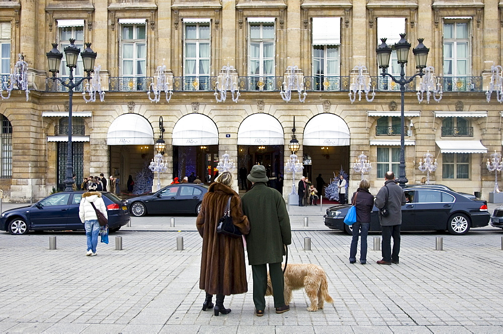 Couple with dog gaze at Ritz Hotel in Place Vendome, Central Paris, France