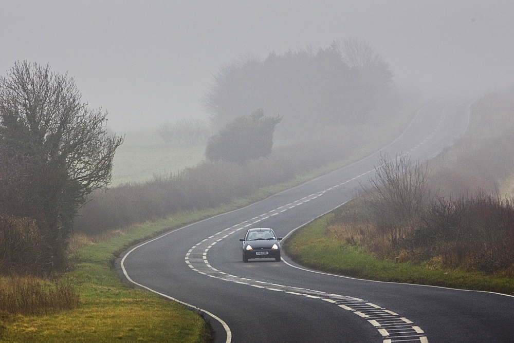 Car drives along foggy road, Oxfordshire,  United Kingdom