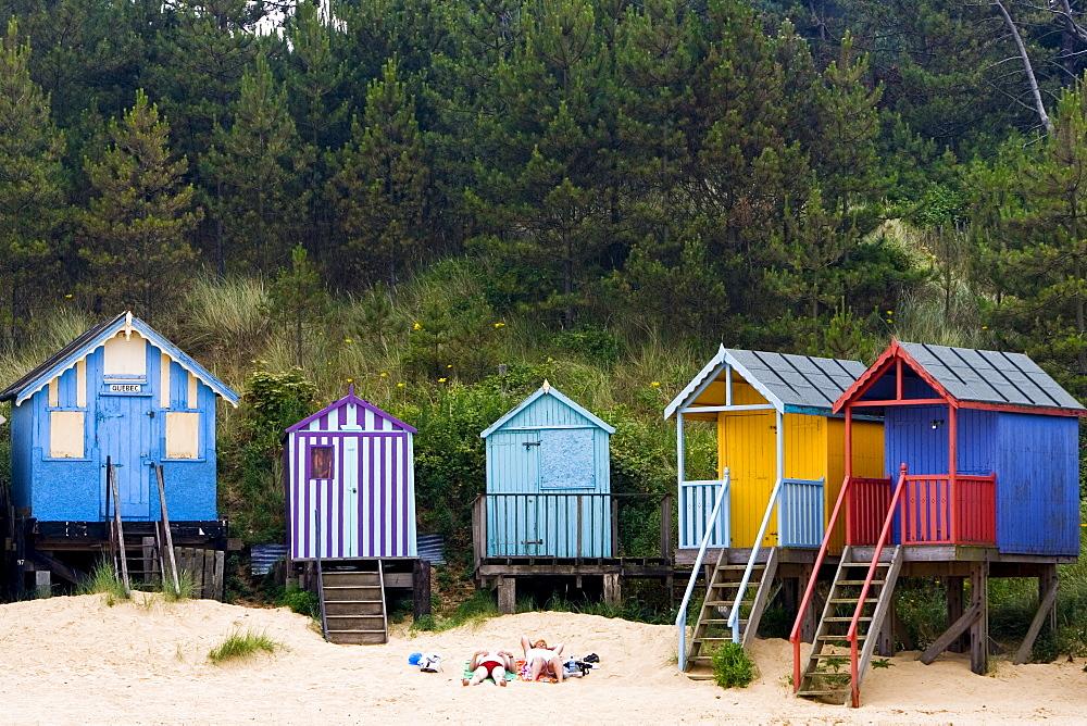 Couple sunbathe outside their beach hut in Wells-Next-The-Sea, Norfolk, United Kingdom