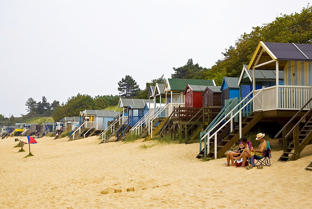Couple sit outside beach hut in Wells, Norfolk, United Kingdom