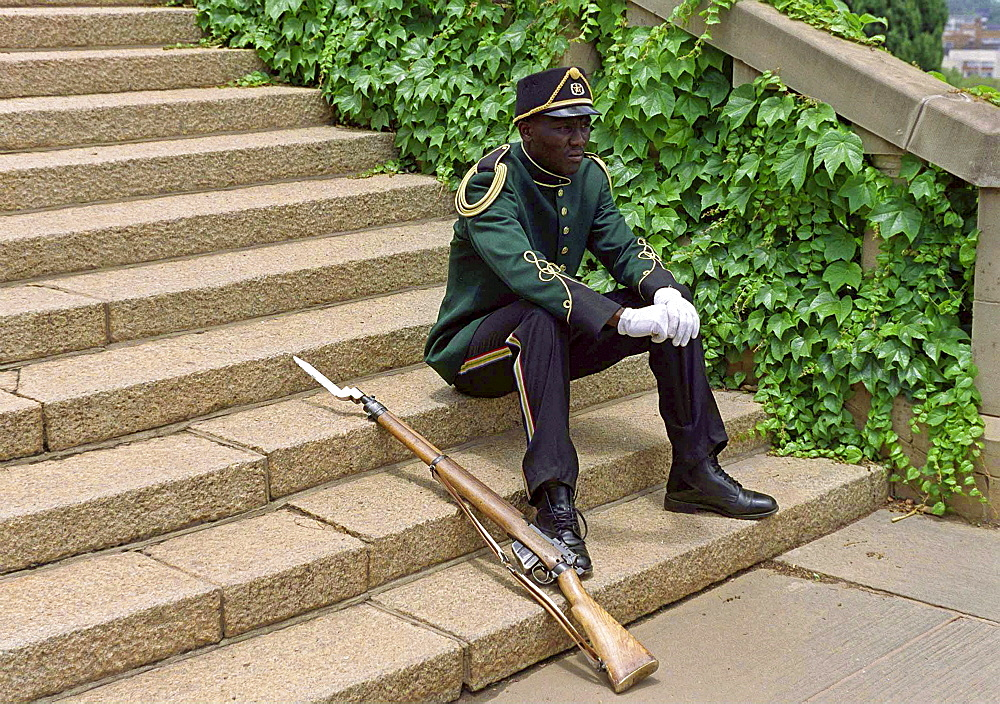 A CEREMONIAL GUARD TAKES A REST AT UNION BUILDINGS, PRETORIA, SOUTH AFRICA