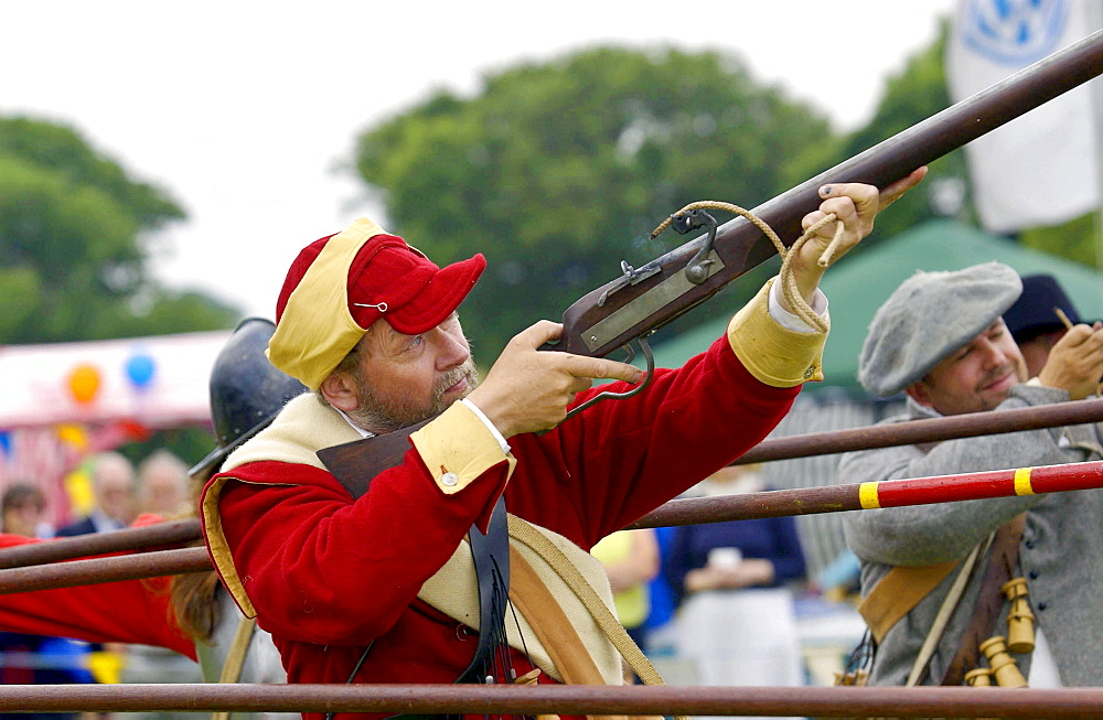 Member of the foot regiment of the sealed knot society firing a musket in the isle of man