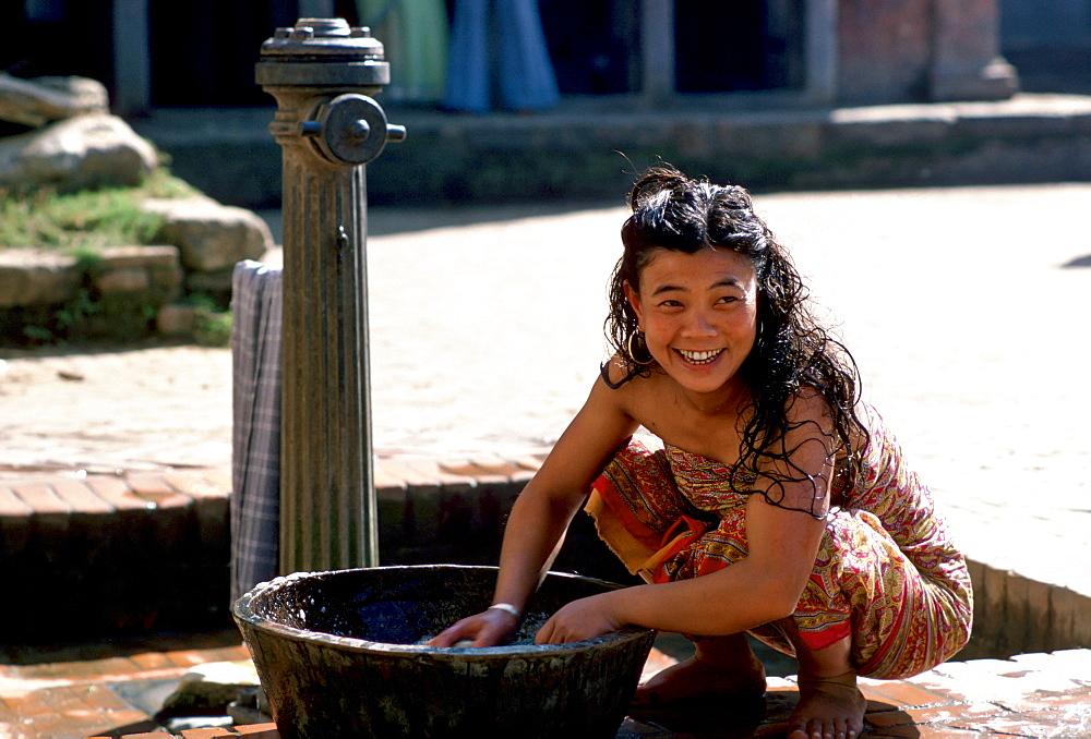 Young woman washing at water pump, Patan, Nepal