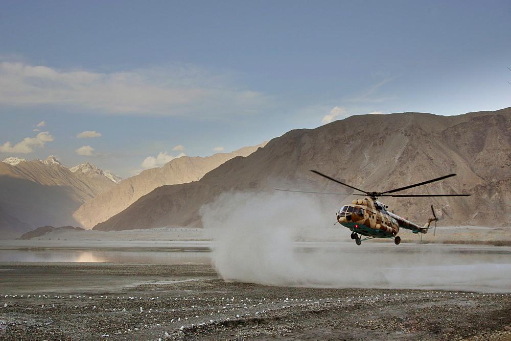Helicopter lands on heliport in valleys of Karokoram Mountains, Skardu Valley, North Pakistan