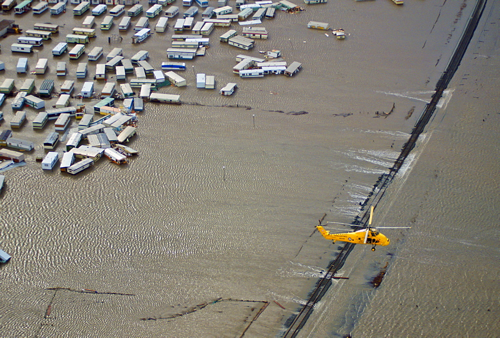 Rescue helicopter flies over flooded caravan park and railway during flooding in North Wales