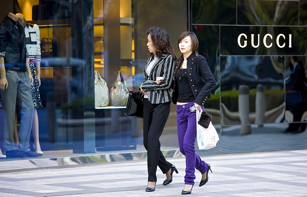 Women outside Gucci deisgner clothes shop, on Nanjing Road, central Shanghai, China