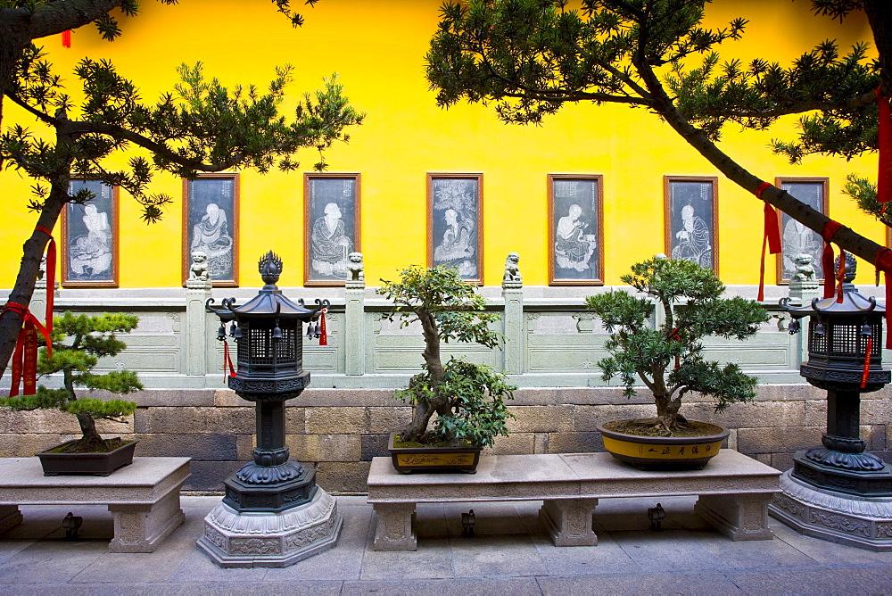 Bonzai trees and bronze lanterns in the courtyard of the Jade Buddha Temple, Shanghai, China