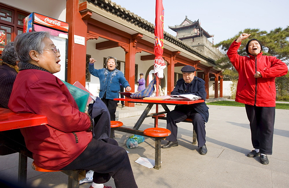 People gather to sing, part of their morning exercise in the park by the City Wall, Xian, China