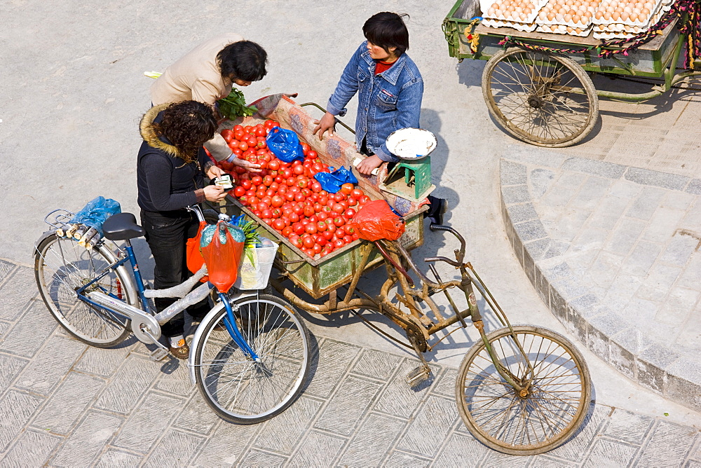 Women buying tomatoes from cart in street market, viewed from the City Wall, Xian, China
