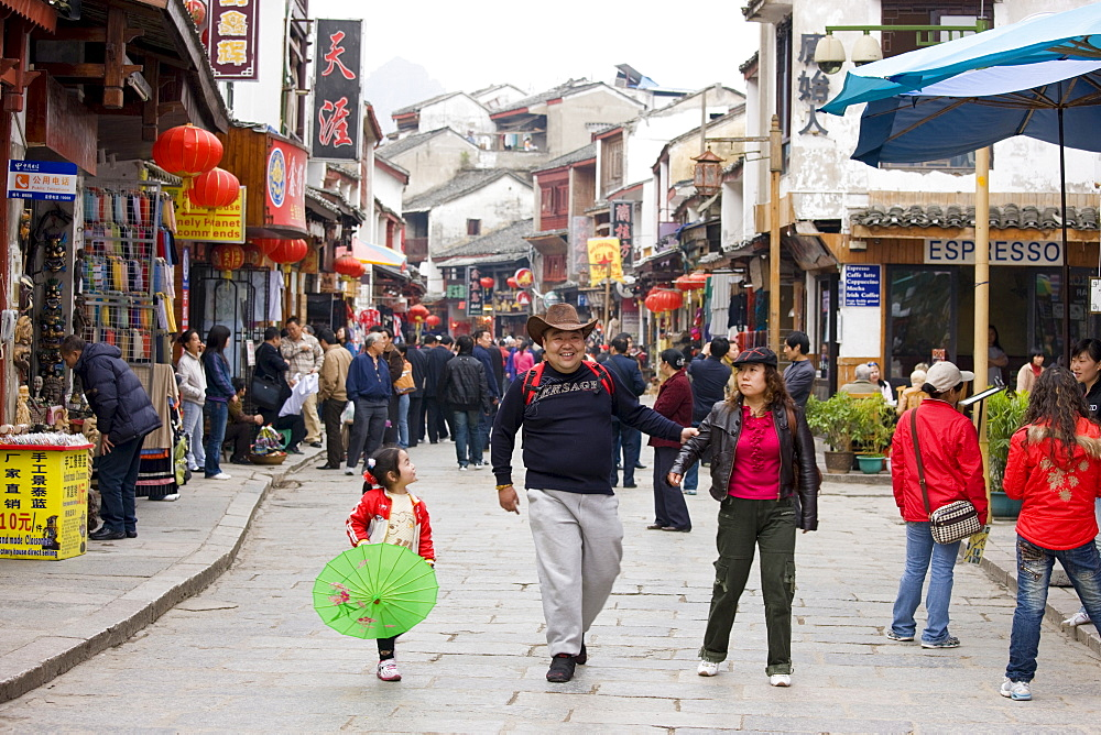 Tourist family in shopping street, Yangshuo. China has a one child policy to limit population.