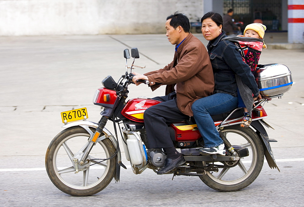 Couple with child on motorbike in Guilin, China. China has a one child family planning policy to reduce population.