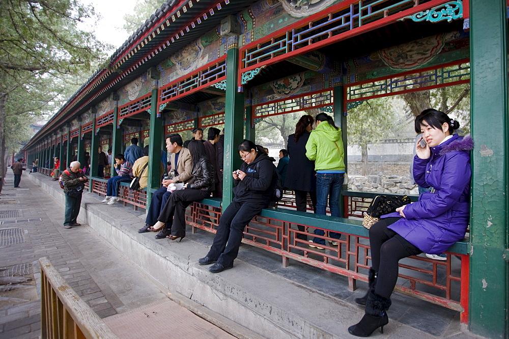 Visitors sit along the Long Corridor (Chang Lang) at The Summer Palace, Beijing, China