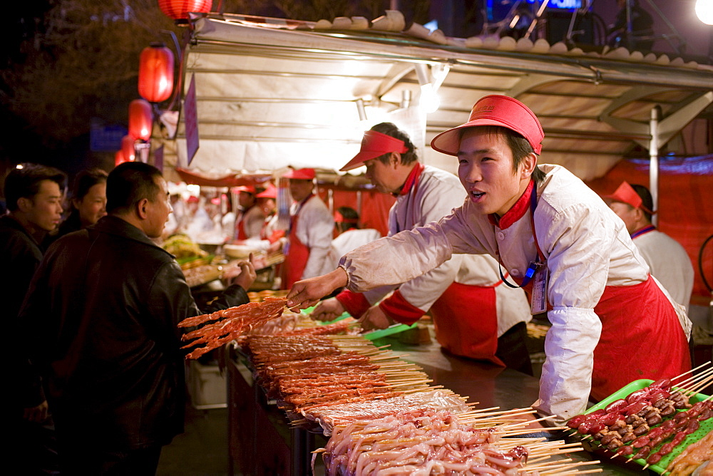 Stall selling meat kebabs in the Night Market, Wangfujing Street, Beijing, China