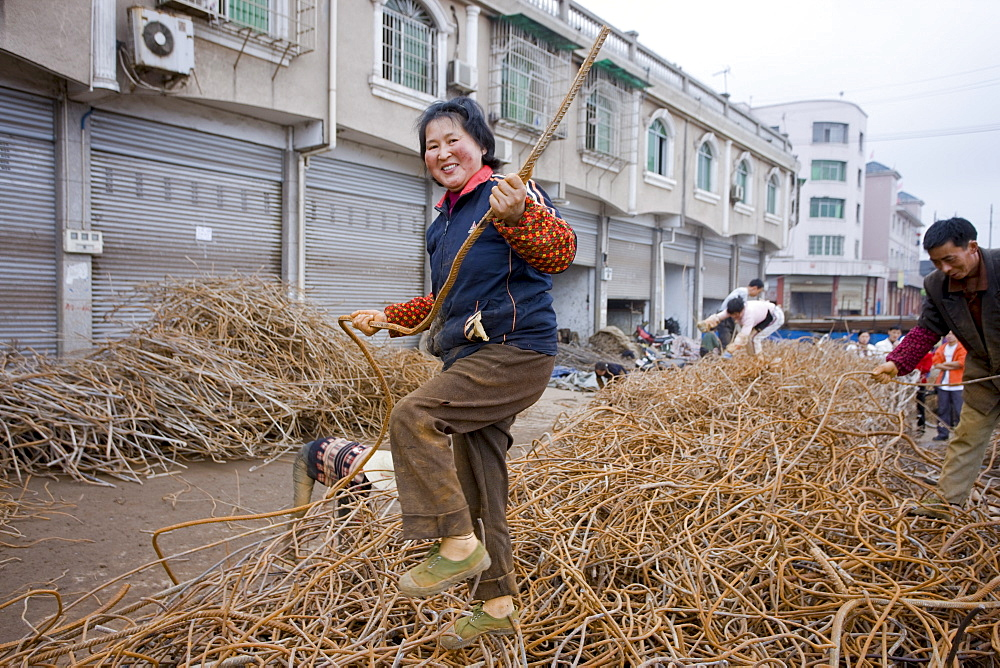 Woman working at metal recycling steel in Dazu County, Chongqing, China