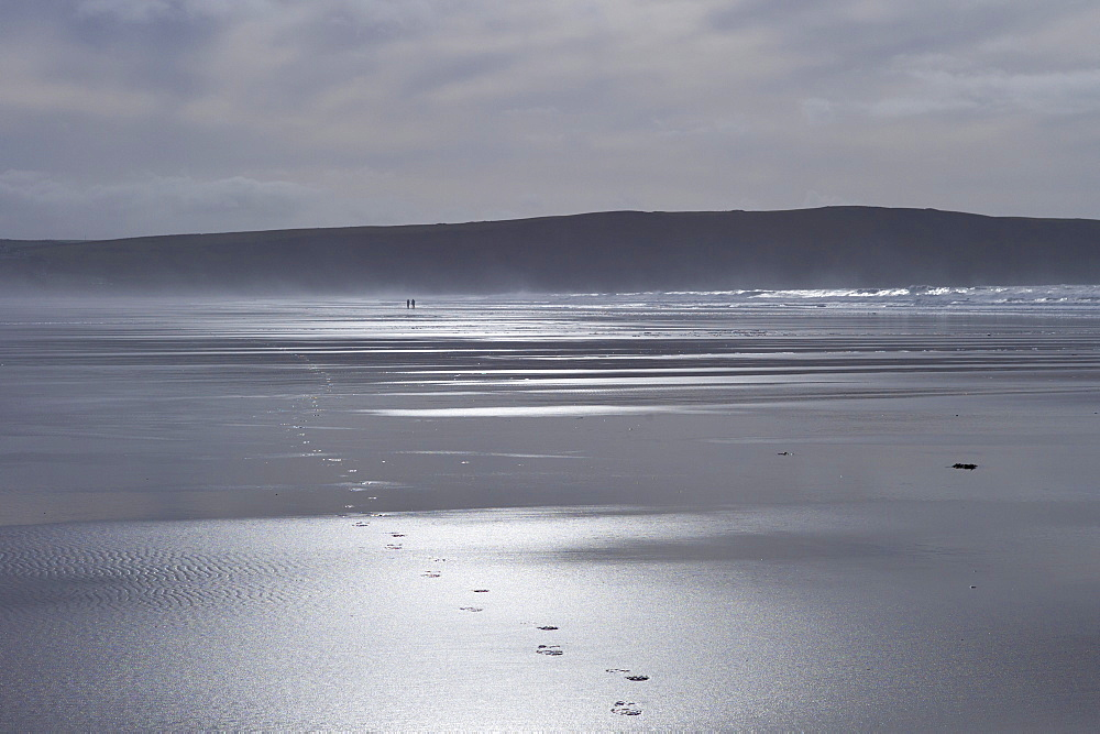 Couple walking on the beach leave footprints in the sand at Woolacombe, North Devon, UK