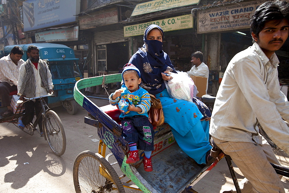 Muslim woman and child in rickshaw in Old Delhi, India