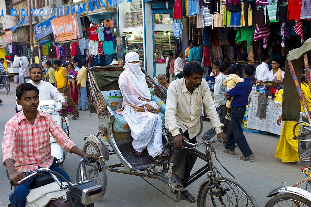 Street scene in holy city of Varanasi, young muslim woman in white burkha rides in rickshaw, Benares, Northern India