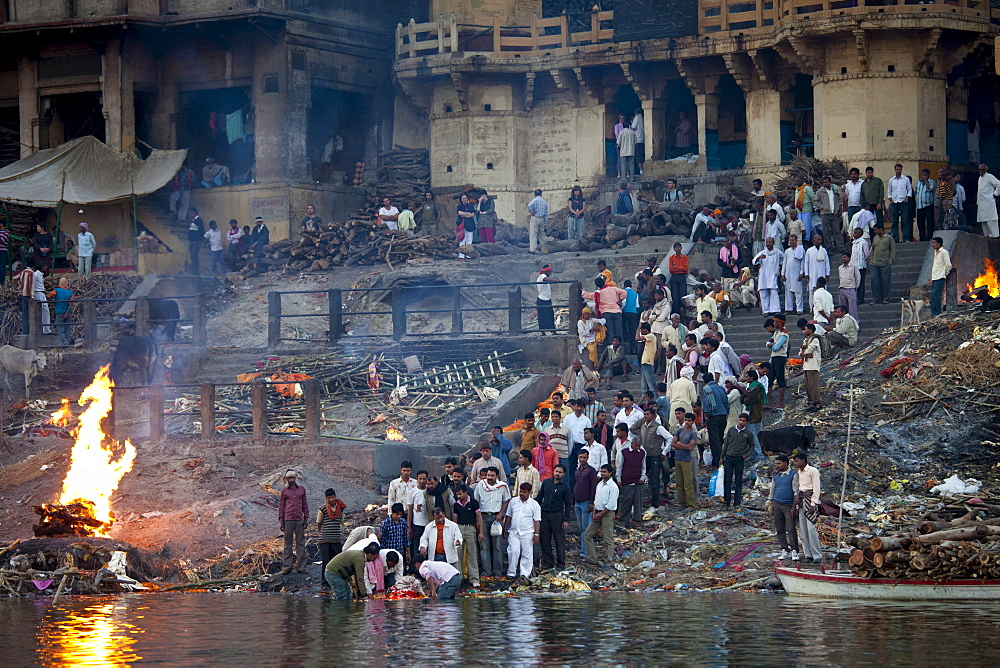 Body bathed in River Ganges and traditional Hindu cremation on funeral pyre at Manikarnika Ghat in Holy City of Varanasi, Benares, India