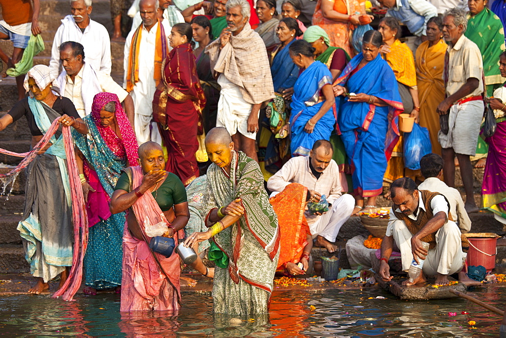 Indian Hindu pilgrims bathing and cleaning teeth in The Ganges River at Dashashwamedh Ghat in Holy City of Varanasi, Benares, India