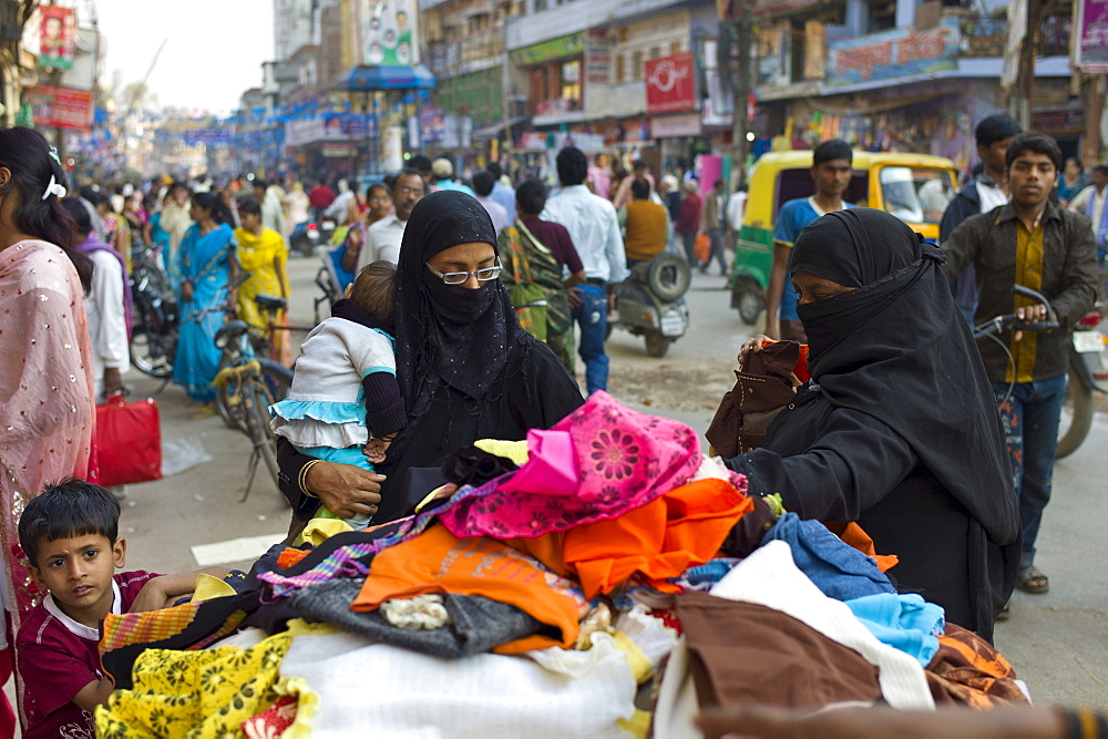 Street scene in holy city of Varanasi, young muslim women in black burkhas shopping with their children, Benares, Northern India