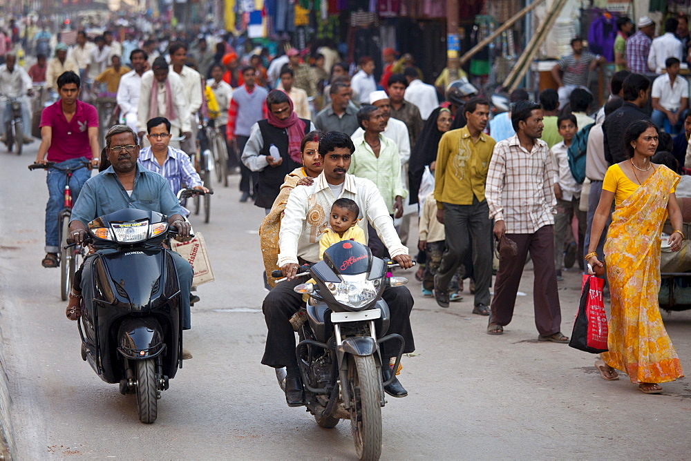 Fathers with children on cycles in crowded street scene during holy Festival of Shivaratri in city of Varanasi, Benares, Northern India