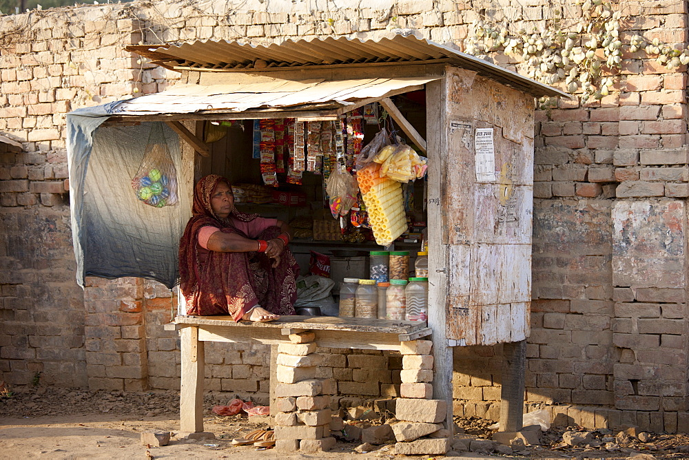 Indian woman stallholder selling sweets and toys at Sarnath near Varanasi, Benares, Northern India