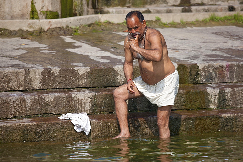 Indian Hindu man bathing and cleaning his teeth in the River Ganges by Kshameshwar Ghat in holy city of Varanasi, India