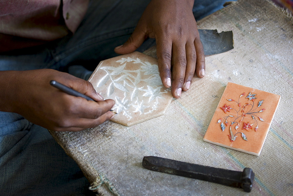 Skilled craftsman at work making Pietra Dura gem souvenirs using traditional old-fashioned methods in Agra, India