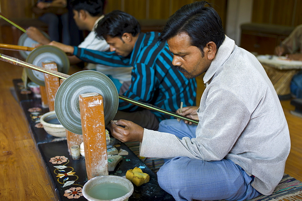 Skilled craftsmen at work making Pietra Dura souvenirs using traditional old-fashioned grinding wheel in Agra, India