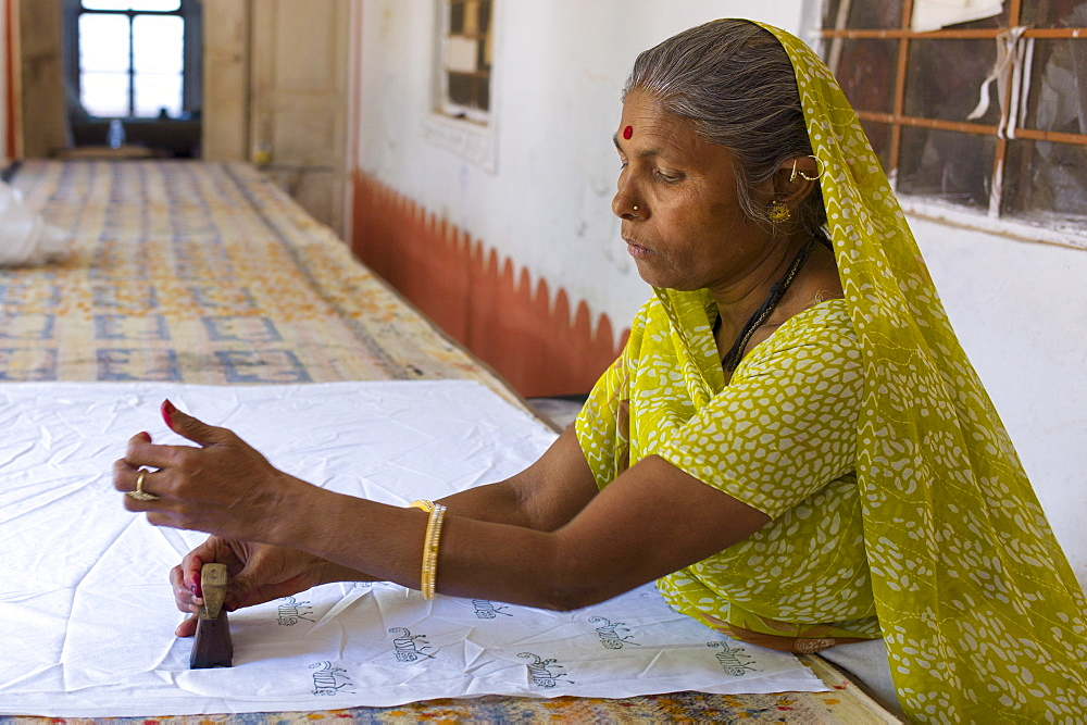 Indian woman die stamping textiles at Dastkar women's craft co-operative, the Ranthambore Artisan Project, in Rajasthan, India