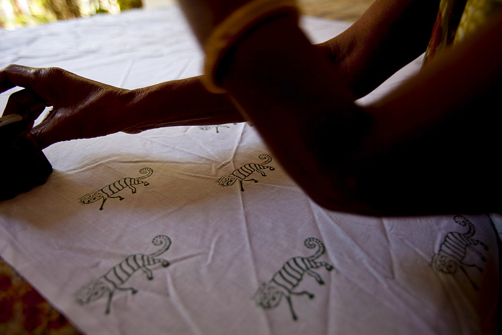 Indian woman handblock printing textiles with tiger motif at Dastkar women's craft co-operative, Ranthambore Artisan Project, Rajasthan, India
