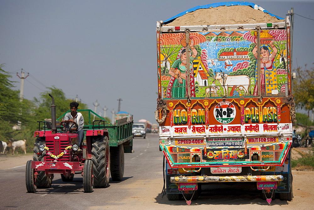 Indian farmer drives tractor past Tata trucks at Rasulpura in Sawai Madhopur, Rajasthan, Northern India