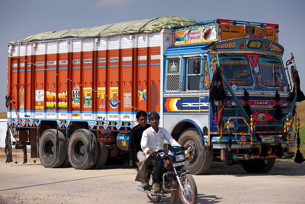 Indian motorcyclist rides past Tata trucks at Rasulpura in Sawai Madhopur, Rajasthan, Northern India