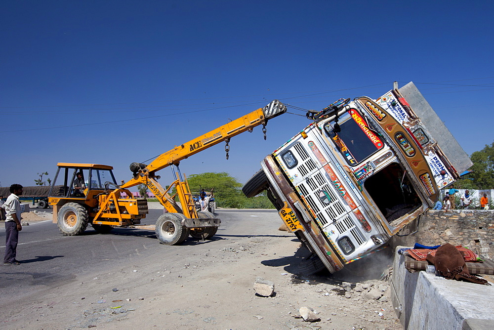 TATA Truck overturned in traffic accident lifted by ACE lifting gear on Delhi to Mumbai National Highway 8 at Jaipur, Rajasthan, India