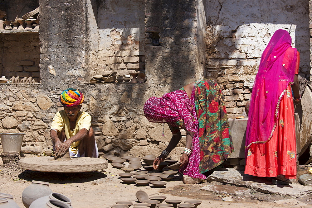 Indian potter in traditional Rajasthani turban works at home with his family making clay pots in village of Nimaj, Rajasthan, Northern India
