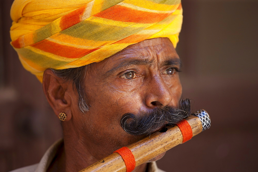 Hindu musician playing flute wind instrument at Mehrangarh Fort at Jodhpur in Rajasthan, Northern India - 1161-5045
