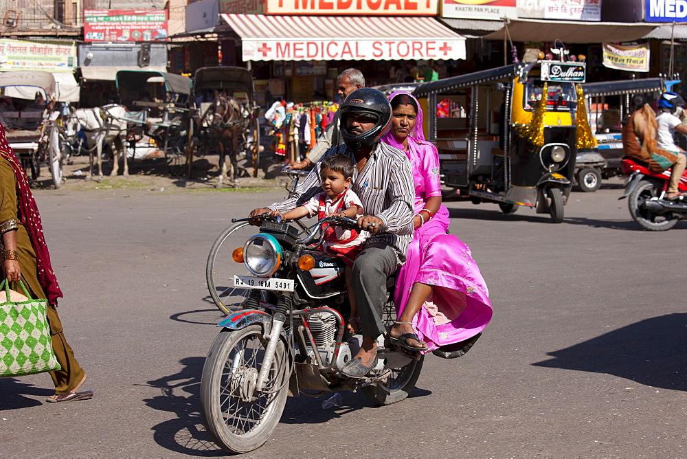 Indian family riding motorcycle, street scene at Sardar Market at Girdikot, Jodhpur, Rajasthan, Northern India