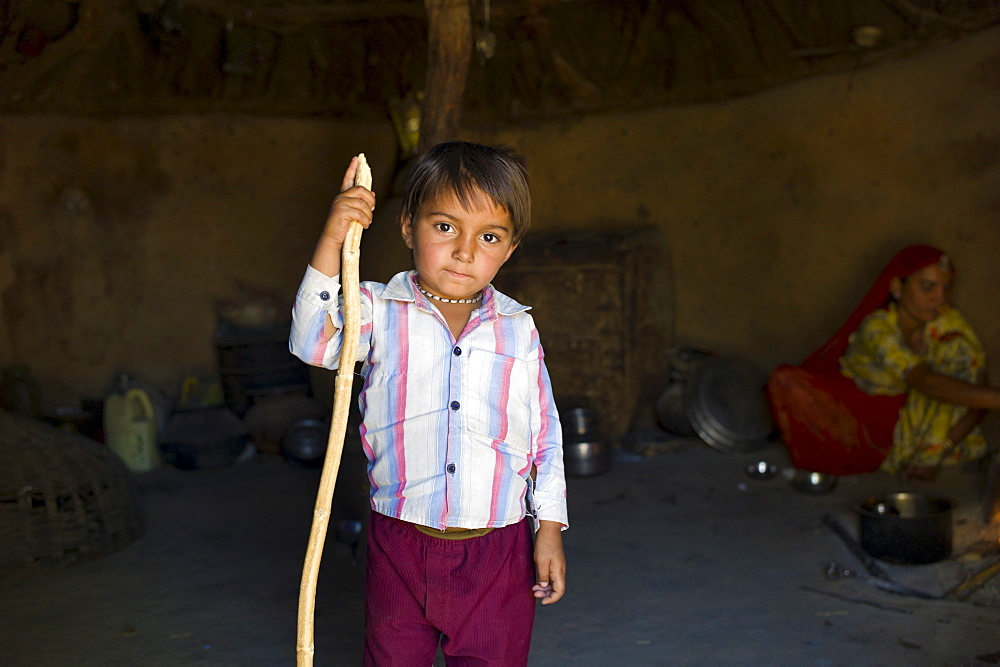 Indian boy inside his home made of mud bricks coated in cow dung in Bishnoi tribe village near Rohet in Rajasthan, Northern India