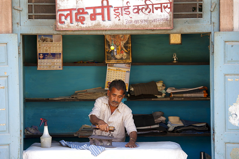 Indian man pressing clothes in his workroom in Narlai village in Rajasthan, Northern India