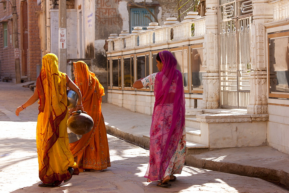 Rajasthani women carrying water pots in the village of Narlai in Rajasthan, Northern India