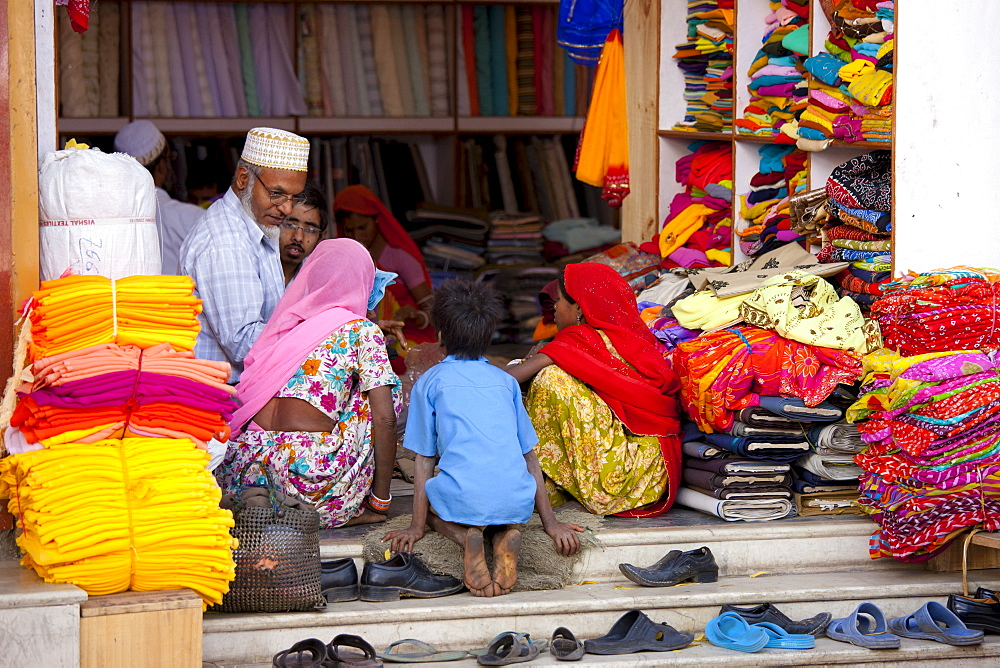 Indian family shopping for children's clothes in old town in Udaipur, Rajasthan, Western India, Hindus and Muslims together.