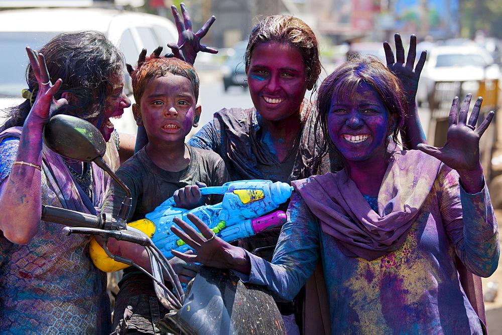 Indian woman and child celebrating annual Hindu Holi festival of colours with powder paints in Mumbai, formerly Bombay, Maharashtra, India