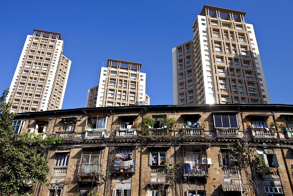 Old traditional tenement housing in the shadow of new modern high rise apartment blocks at Mahalaxmi in Mumbai, Maharashtra, India