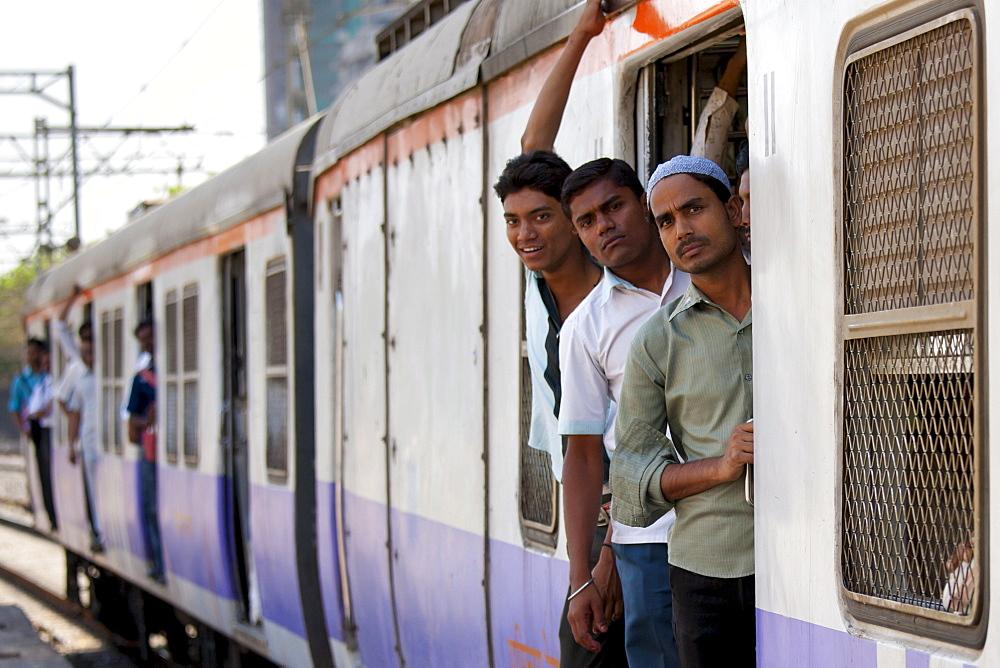 Workers on crowded commuter train of Western Railway near Mahalaxmi Station on the Mumbai Suburban Railway, India
