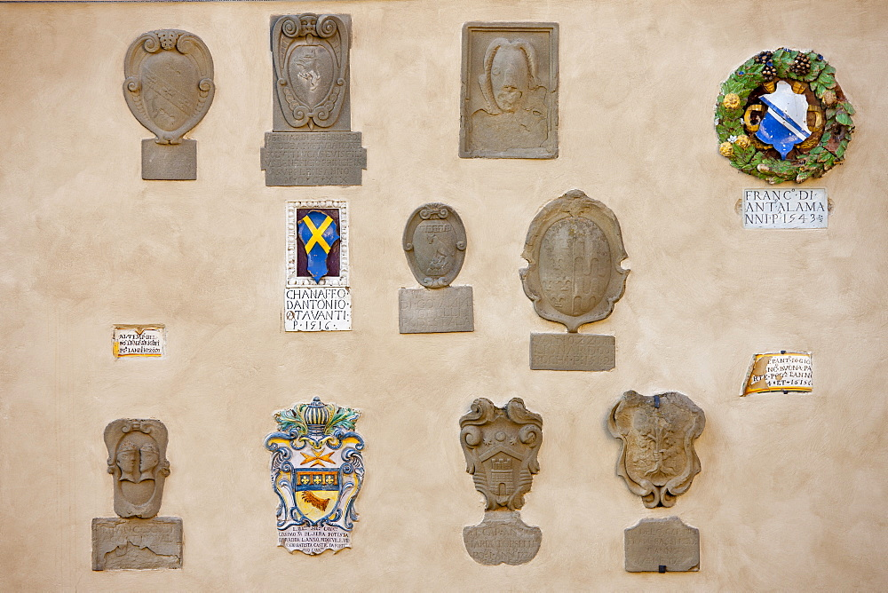 Badge crests on the Town Hall, The Palace of the Podestra, in Piazza Francesco Ferrucci, Radda-in-Chianti, Tuscany, Italy