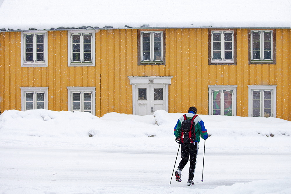 Man with walking poles passes traditional wooden buildings on Storgata in the quaint area of Tromso, Arctic Circle, Northern Norway