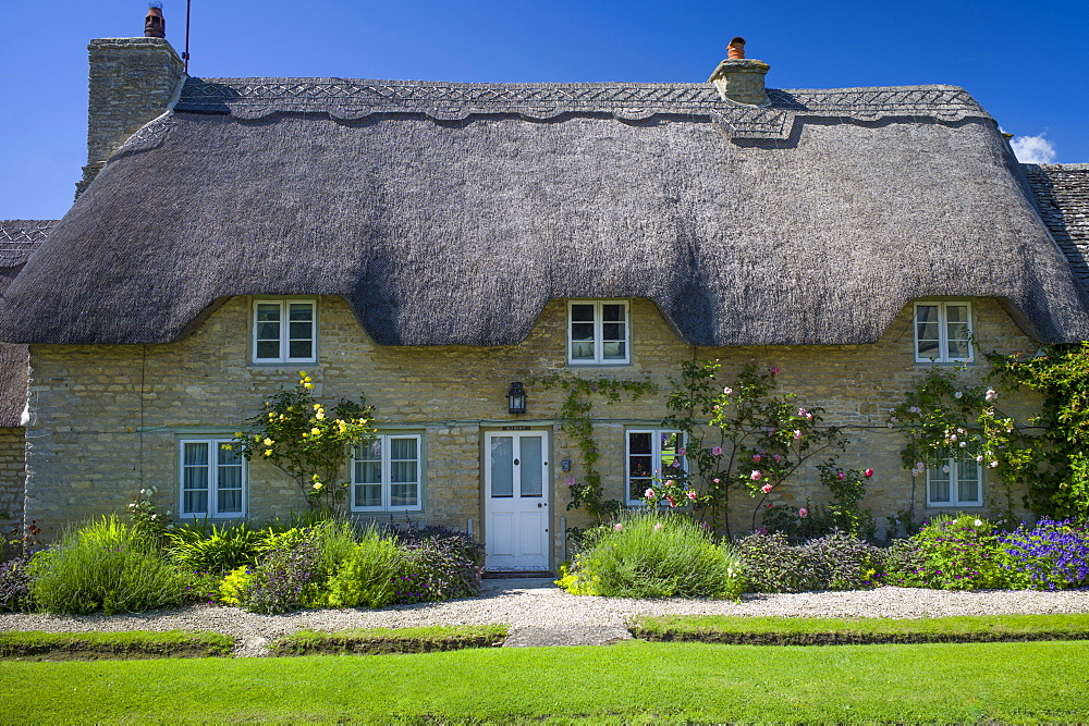 Quaint traditional thatched cottage in Minster Lovell in The Cotswolds, Oxfordshire, UK
