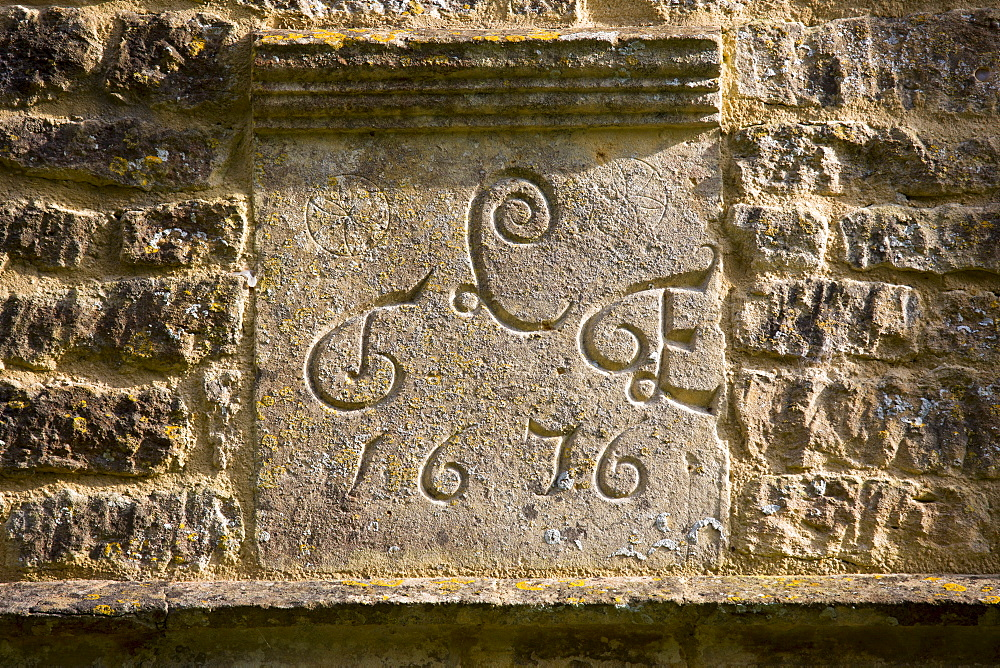 Date 1676 of traditional 17th Century cottage of old Cotswold stone at Taynton in The Cotswolds, Gloucestershire, UK