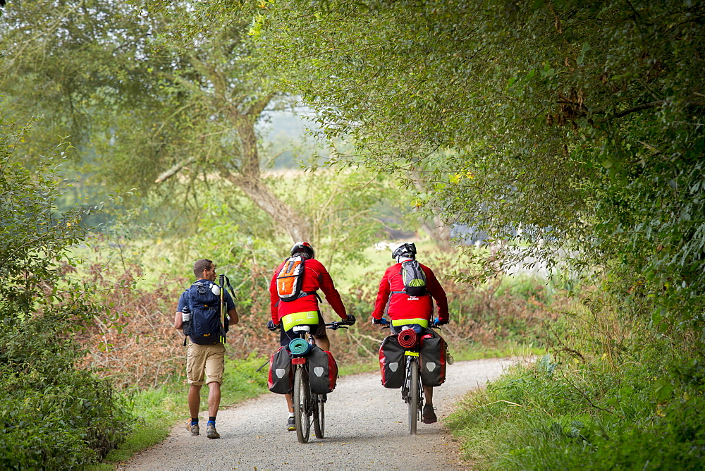 Cyclists and walker on the Camino de Santiago Pilgrim's route to Santiago de Compostela in Galicia, Spain